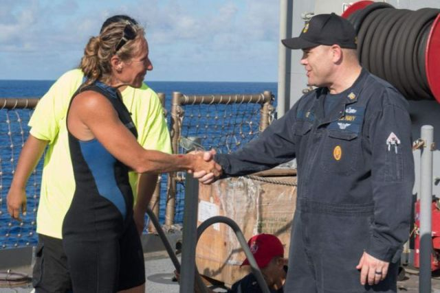 Jennifer Appel stands on a boat and shakes hands with USS Ashland Command Master Chief Gary Wise.