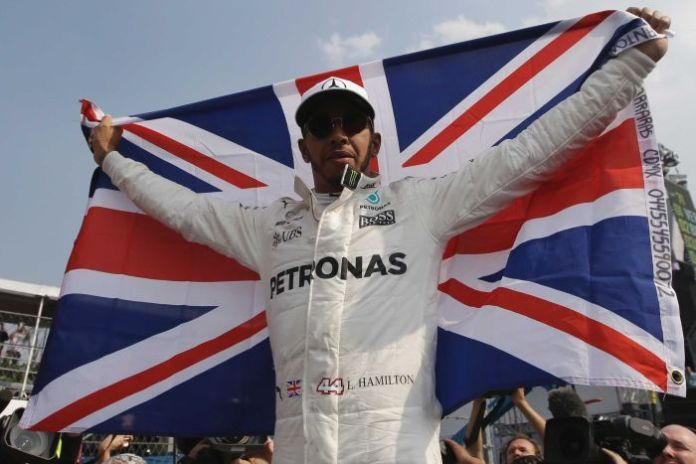 Lewis Hamilton, with helmet off, flies the British flag.