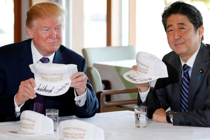 Donald Trump and Shinzo Abe hold hats they signed reading 'Donald & Shinzo Make Alliance Even Greater'.