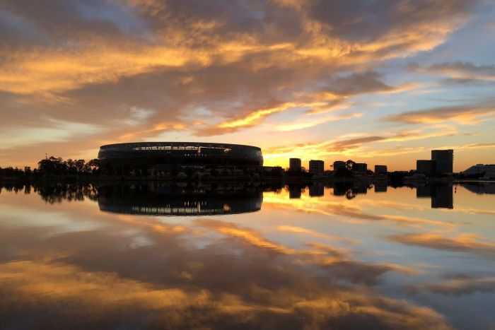 A wide shot looking over the Swan River showing Perth Stadium at dawn with clouds reflected on the water.