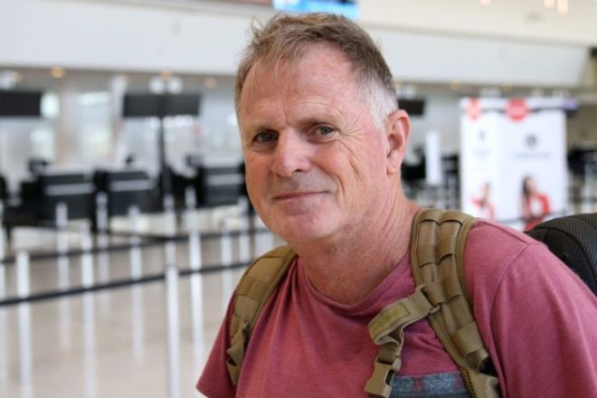 Alan Fairweather stands in the airport wearing a backpack and t-shirt.