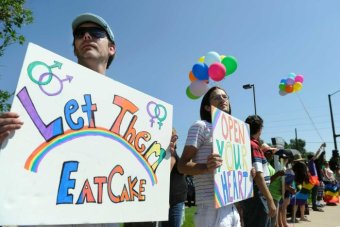 "Protesters hold colourful ""Let them eat cake"" and ""open your heart"" signs."