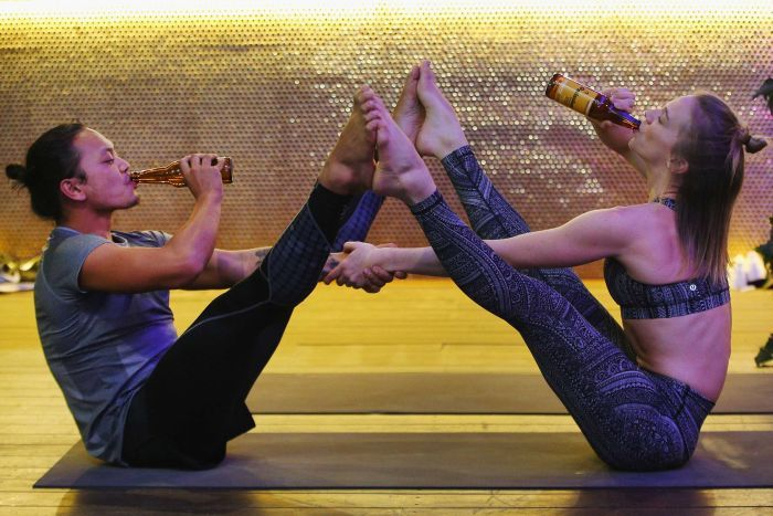 Two participants in Melbourne beer yoga class doing poses while drinking beer.