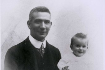 Black and white photo of Dr John Gilruth with his baby daughter on his knee.