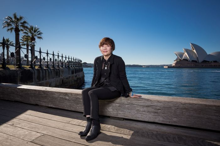 Biennale of Sydney director Mami Kataoka sits beside Sydney Harbour with Sydney Opera House in the distance behind her.