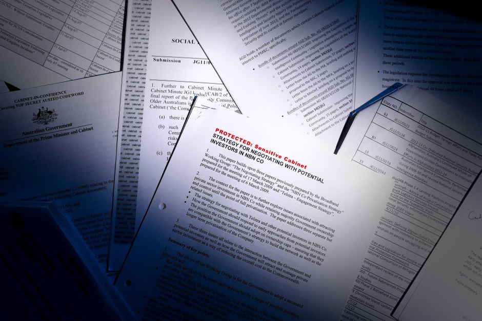 A pile of papers are scattered on a desk. A beam of light cuts across, with the top right and bottom left corners in shadow.