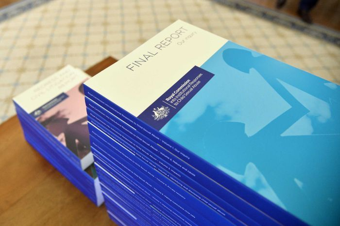 The volumes of the Child Abuse Sexual Abuse report stacked on a table.