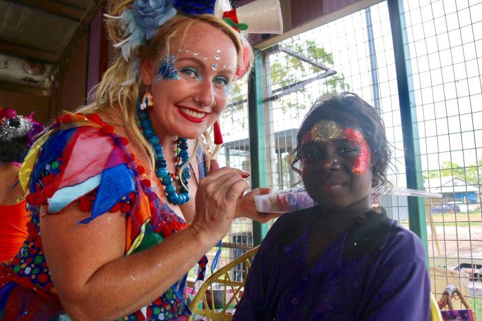 A little girl gets a sparkly Aboriginal flag painted on her face by a woman in a colourful fairy costume.