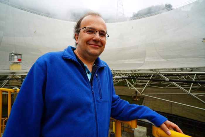 CSIRO astrophysicist George Hobbs looks at camera with FAST radio telescope behind him