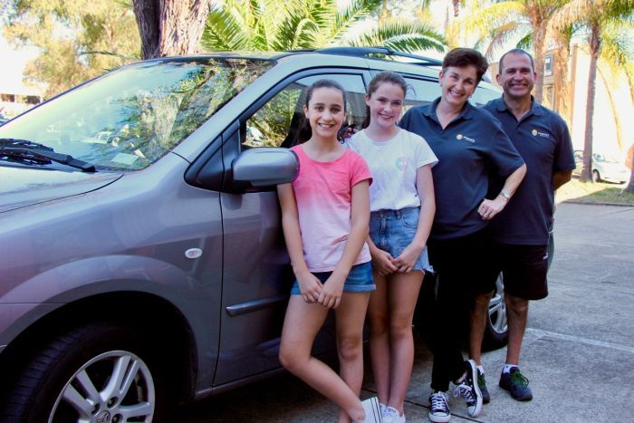 Two parents and their daughters outside a car