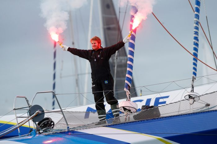 French skipper Francois Gabart waves flares on his trimaran.
