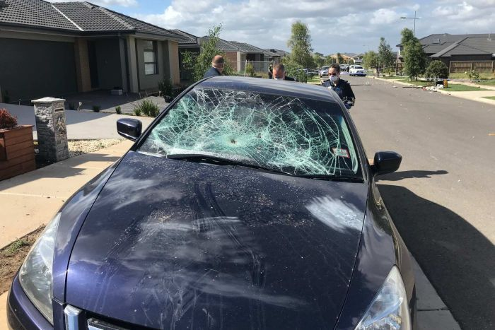 A car's front windshield is smashed by partygoers in Werribee.