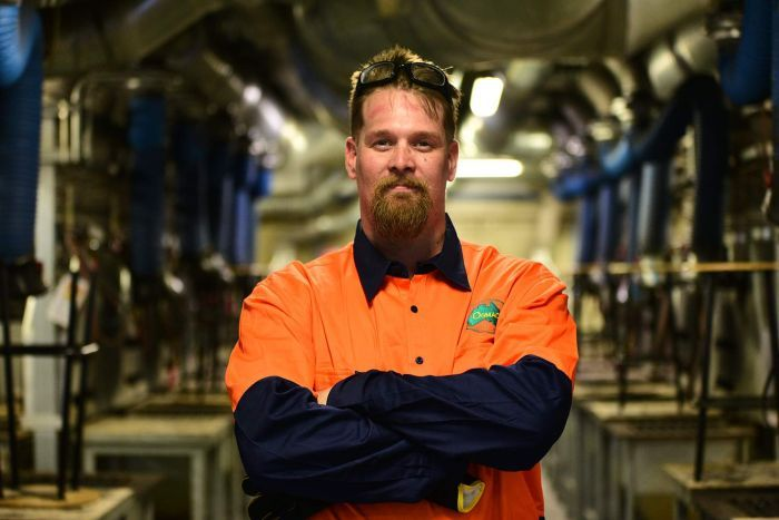 Nathanial Bradford stands and smiles with crossed arms at his Brisbane workplace.