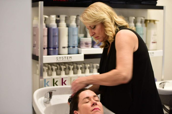 Apprentice Veronica Ford washes a woman's hair in her workplace, a hair salon in Brisbane.