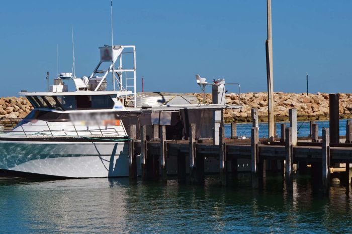 A boat is moored at the end of a pier.