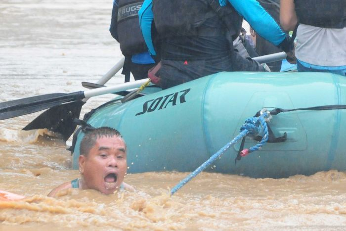 A man clings onto the rope of a rescue boat as residents are evacuated from their homes due to heavy flooding
