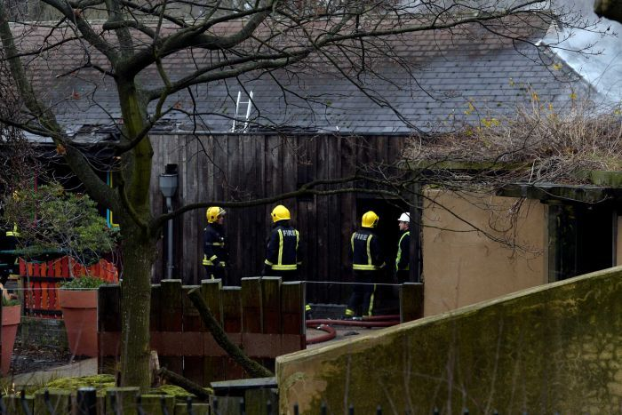 Firefighters stand outside a blackened building