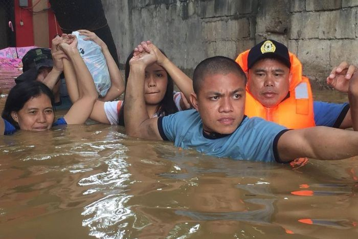 Three police officers help hold the hands and belongings of two women in brown floodwaters up to their necks