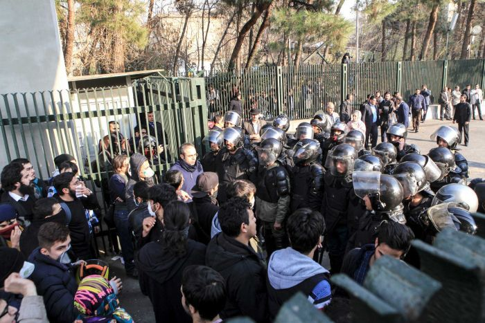 A group of protestors faces off against armoured police.