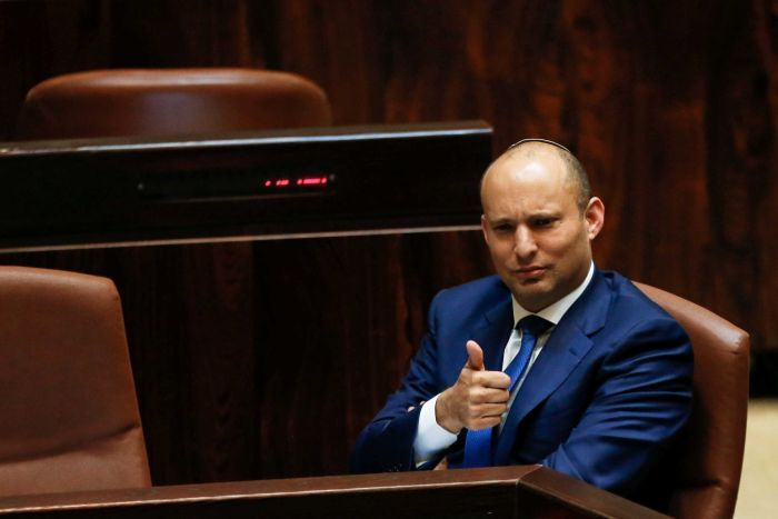 Naftali Bennett sitting in a blue suit gives a thumbs up sign.