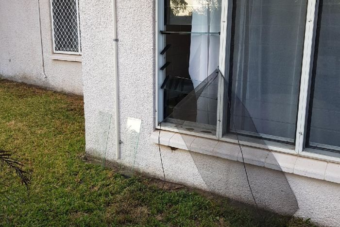 The exterior of a ground-floor unit with a fly screen torn open and glass louvres broken.