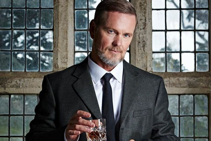 Craig McLachlan in a dark suit holding a glass of whisky