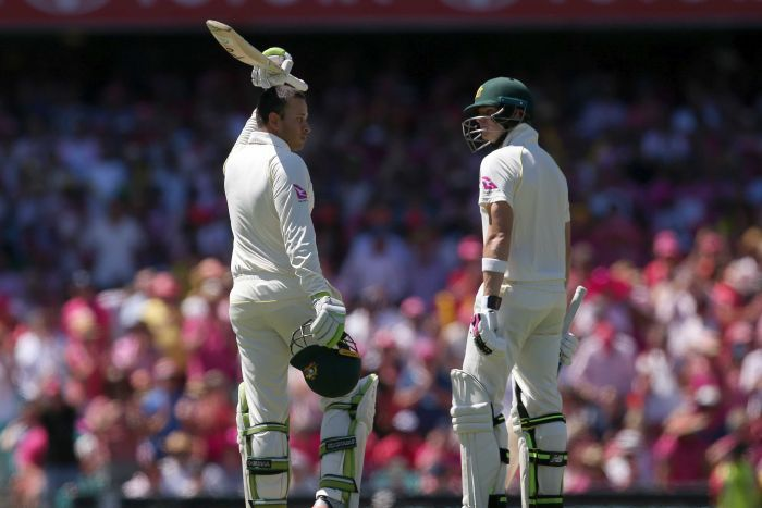 Usman Khawaja raises his bat while Steve Smith looks at him out on the SCG.