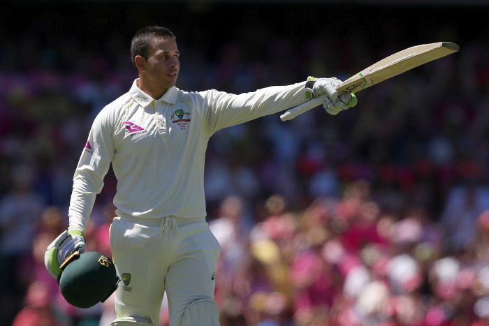 Usman Khawaja points his bat while holding his helmet in his other hand.