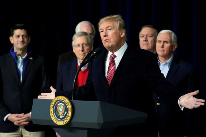 Donald Trump speaks at a podium with his colleagues standing around him.