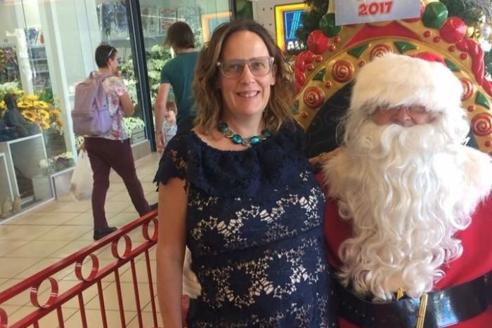Expectant mum Alina Tooley stands next to a shopping mall Santa
