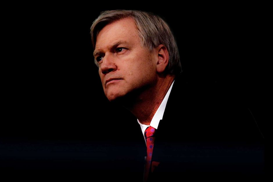 Andrew Bolt, wearing a suit and red tie, glances sideways. The background is dark black.