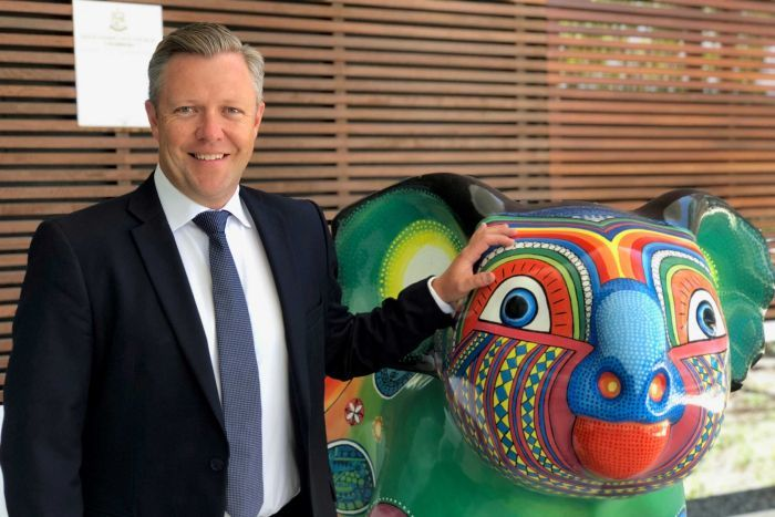 Cr Cameron Caldwell rests his hand on a colourfully painted koala statue