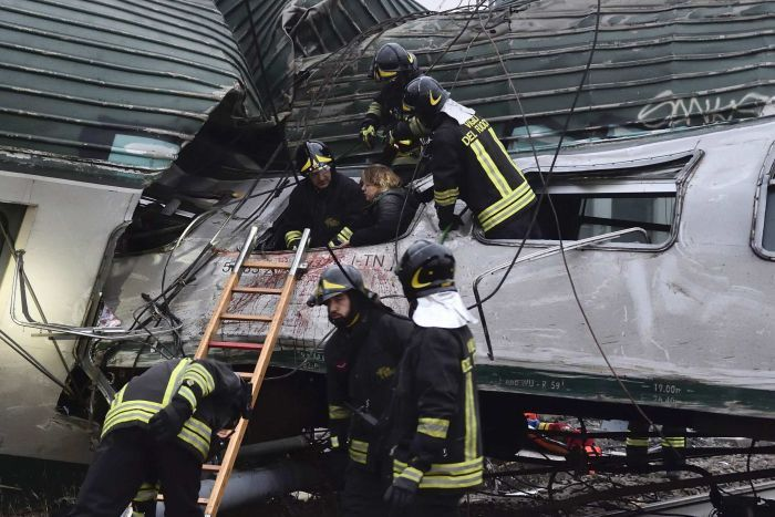 Firefighters help a woman out of the carriage of a derailed train.