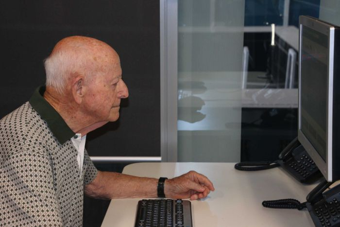 An elderly man is sitting and looking at a computer screen.