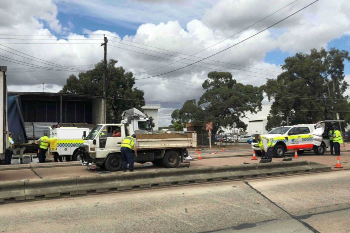 Police inspecting a truck on a sydney road.
