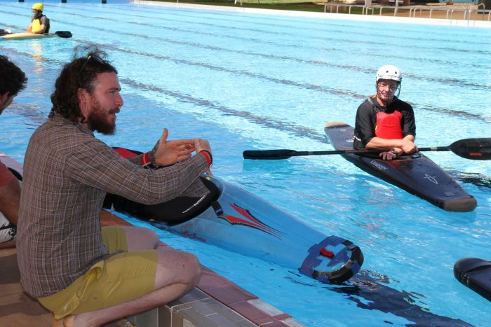 A canoe polo coach talks to players from the side of the Alice Springs pool.