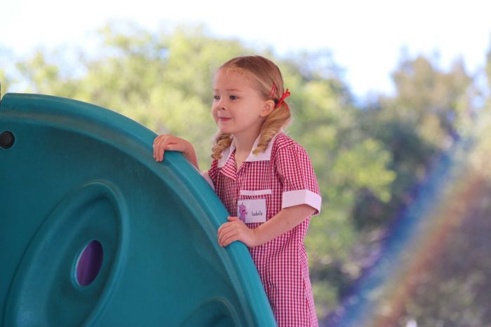 A girl with a nametag reading Isabella climbs on play equipment at a school.