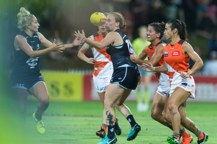 Carlton and GWS players come together in a storm