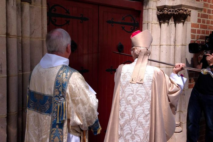 Archbishop Kay Goldsworthy, in dress robes, uses a staff to knock on door of St George's Cathedral as a church official watches.