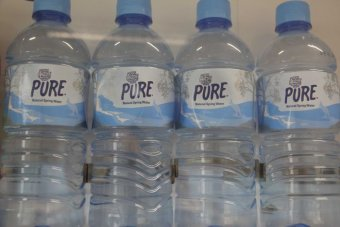 Four bottles of water in a vending machine.