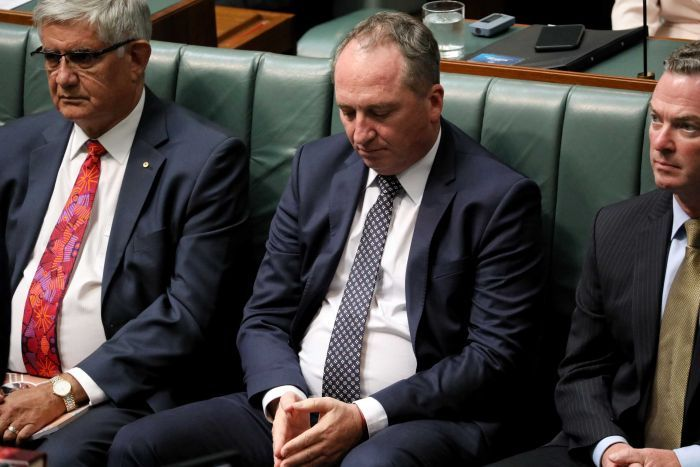Barnaby Joyce gazes down towards his hands, which are clasped in his lap. Next to him are Christopher Pyne and Ken Wyatt