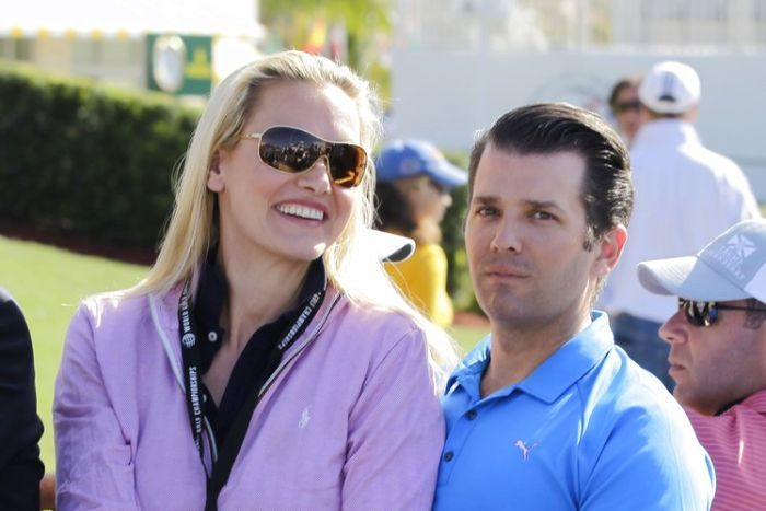 Vanessa and Donald Trump Jr sit very close at an outdoor sports event.