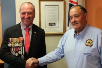 Barnaby Joyce, smiling while wearing military medals, shakes the hand of Bob Chapman from the RSL.