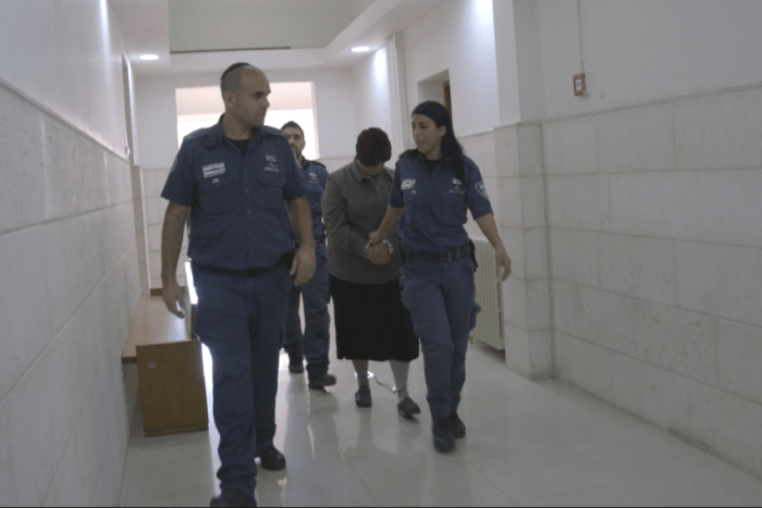 Malka Leifer hangs her head as she is walked down a hallway by police officers.