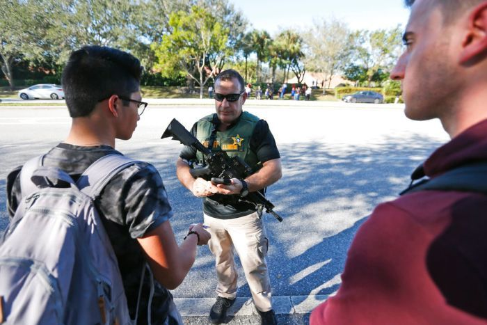 An armed law enforcement officer talks with students.