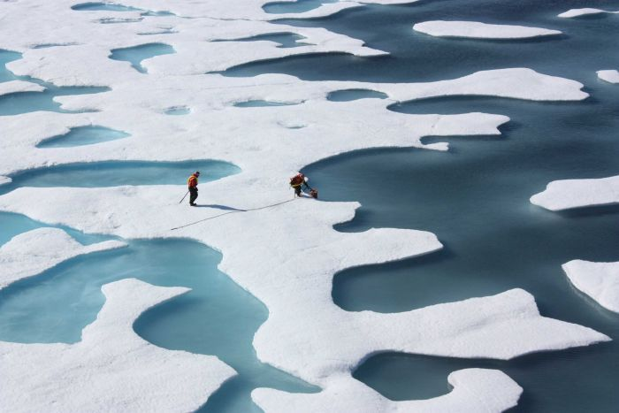 Two people are seen walking on slabs of ice in the Arctic Circle.