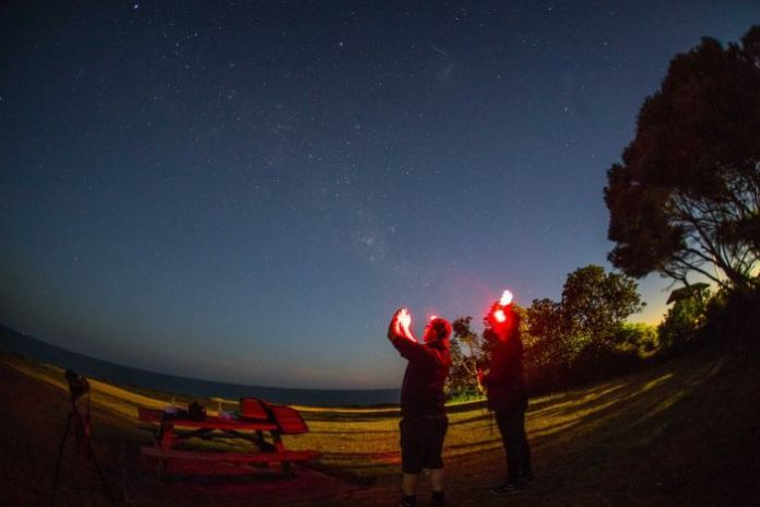 David Finlay and Chris Dengate hold their phones up to the sky at night time