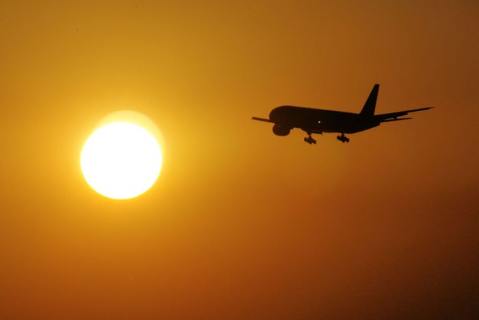 The silhouette of an a aeroplane is seen against a glowing orange sunset.