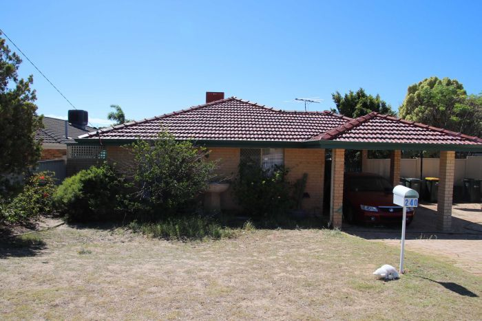 A wide shock of a brick and tile house in Beldon with a car in the carport and under a bright blue sky.