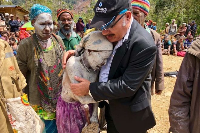 PNG Prime Minister Peter O'Neill hugs a crying woman painted in white body paint